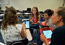 During Institute Day on Aug. 19, Hoffman Estates High School teachers Jessica Schildt (left) and Jen Winfield (right) watch as their colleague demonstrates a task on her iPad.