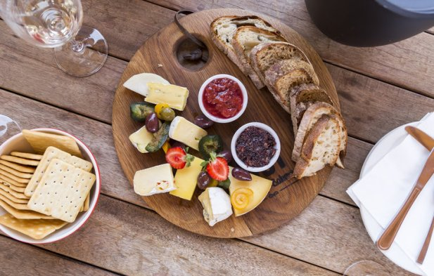 brown platter of different cheeses and bread with crackers and drink