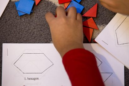 Students do geometric shape puzzles at a Studio of Engaging Math class for kindergartners. (Jesse Costa/WBUR)