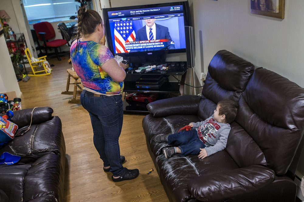Rosa Benitez changes the channel on the television for her 2-year-old son Brandon. (Jesse Costa/WBUR)