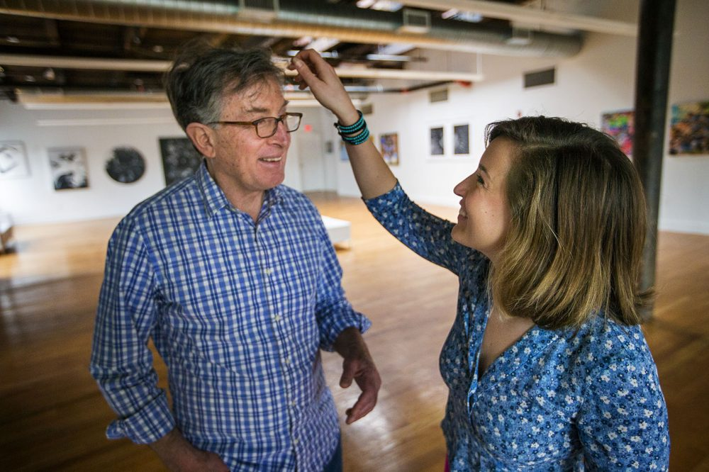 Artist Enrique Flores-Galbis laughs as Olivia Ives-Flores fixes her father's hair for a photo opportunity. (Jesse Costa/WBUR)