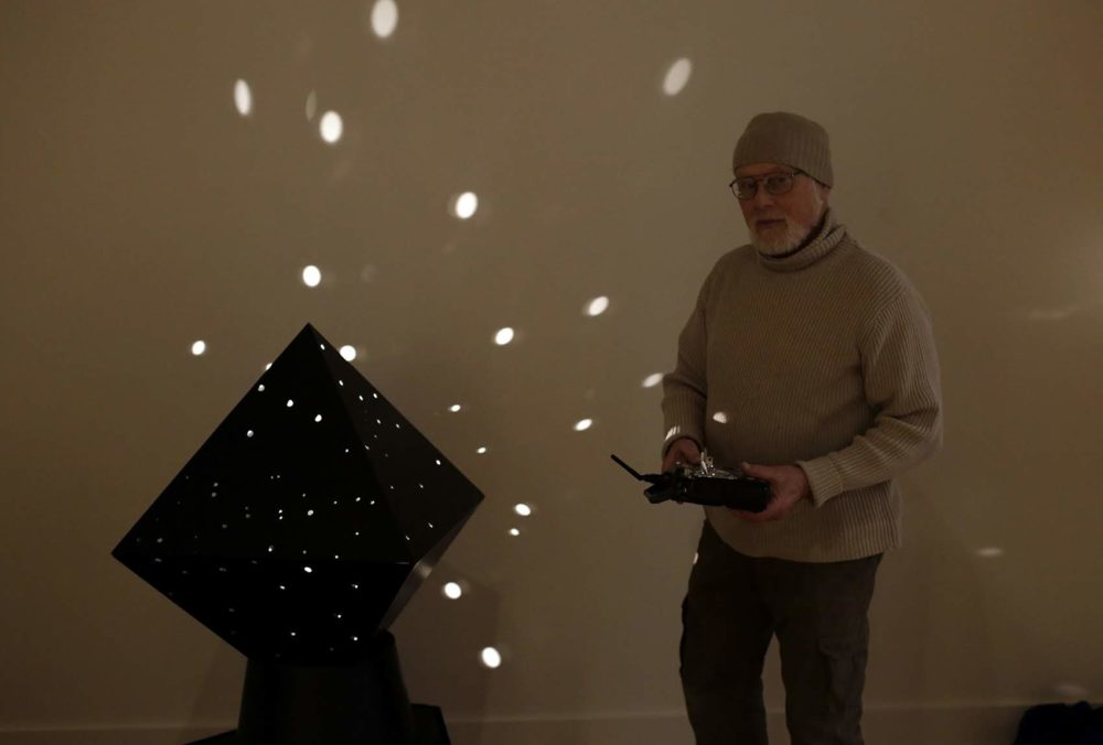 Sculptor John Powell stands with Otto Piene's diamond light robot as he helps with the installation process at the Fitchburg Art Museum. (Hadley Green for WBUR)