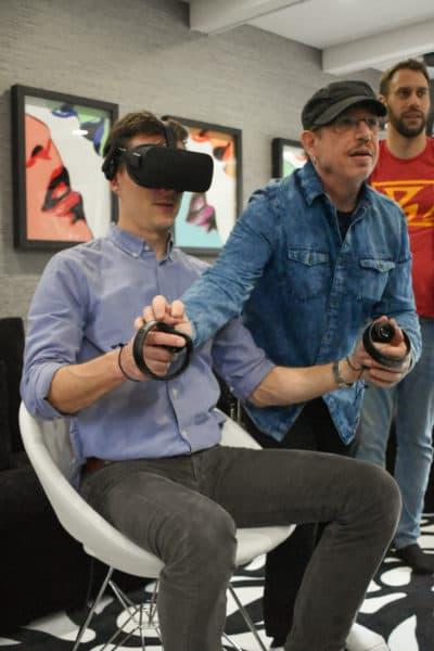 Scott Matalon le muestra al anfitrión Peter O'Dowd cómo operar controladores de realidad virtual de mano.  (Allison Hagan / Aquí y ahora)