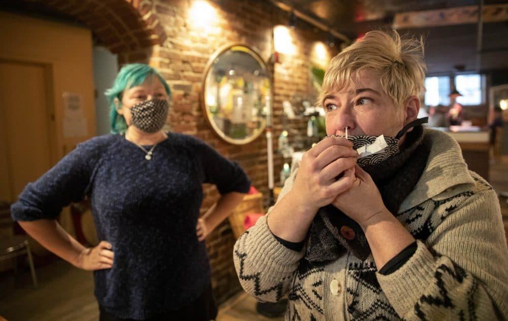 Grendel's owner Kari Kuelzer swabs her nose for a pooled coronavirus test for the restaurant's staff.  (Robin Lubbock/WBUR)