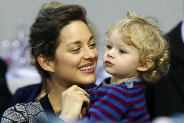 Actress Marion Cotillard and son Marcel cheer for husband and father Guillaume Canet who won a show jumping prize at the Gucci Paris Masters 2012 in Paris