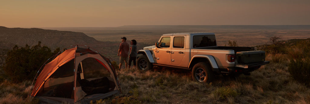 2020 Jeep Gladiator with people and tent beside it looking over a cliff