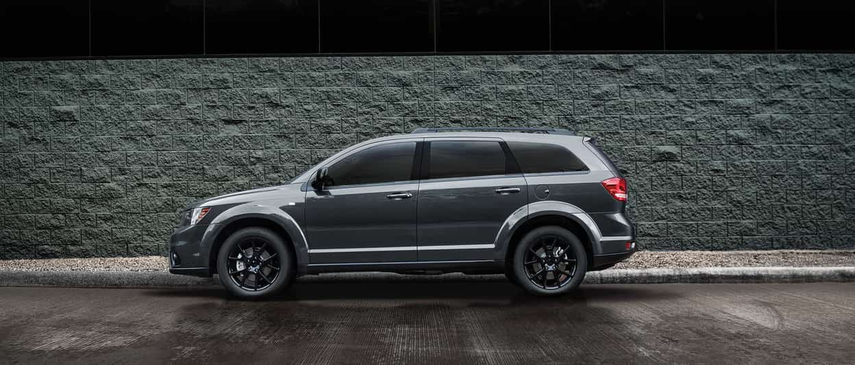2019 Dodge Journey in grey side parked with a shadowy side profile to the left