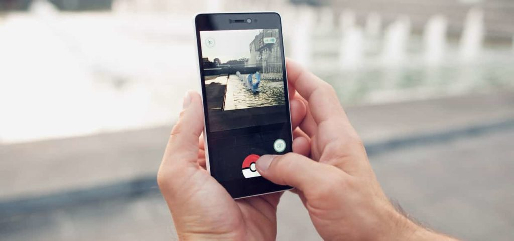 Pokemon Go playing game on mobile phone with blurred background closeup. Catch a Pokemon in real world.
