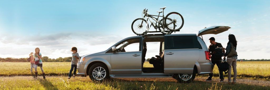 2019 Dodge Grand Caravan side proifle with bikes on the top, parents at the back and kids running in front