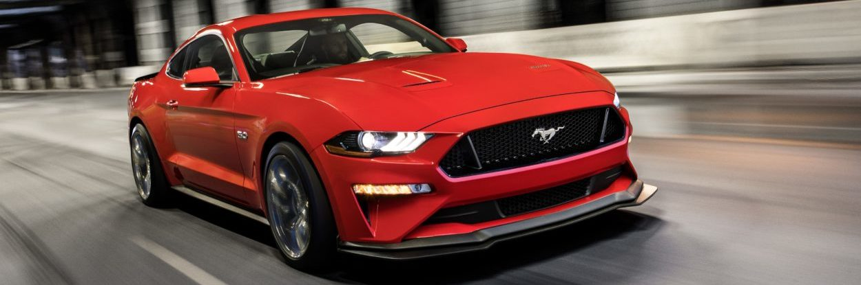 A red 2019 Ford Mustang speeds through an urban tunnel