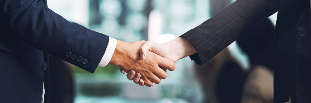 Cropped shot of a businessman and businesswoman shaking hands in a modern office