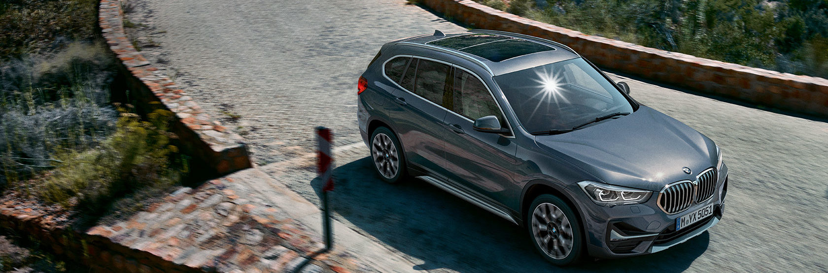 BMW X1 in slate grey driving on cobblestone road, shot from above