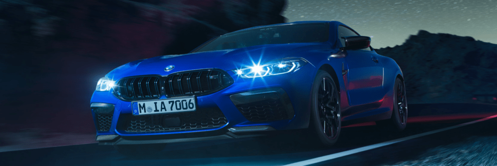 BMW M8 Coupe with laserlight headlights shining bright driving on a country road
