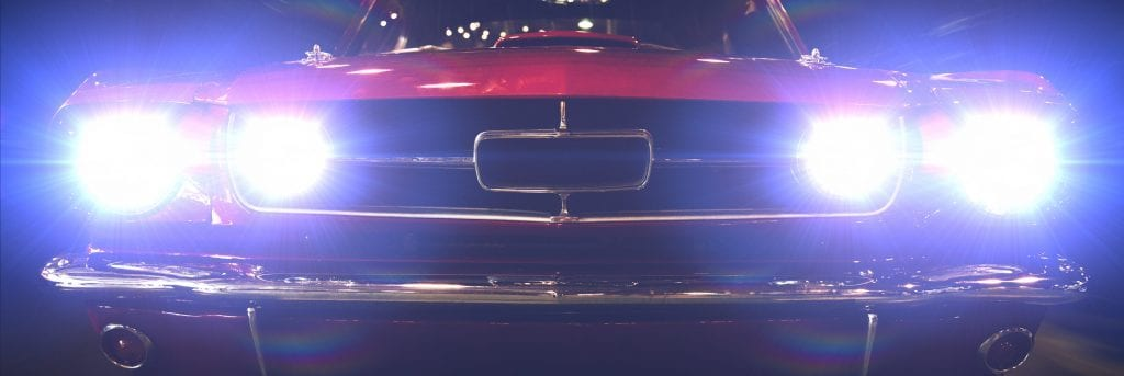 Close-up of retro car with bright headlights on.