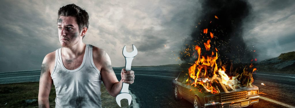 Man holding a wrench with his car on fire in the background. Needs help to repair the car. Car insurance concept.