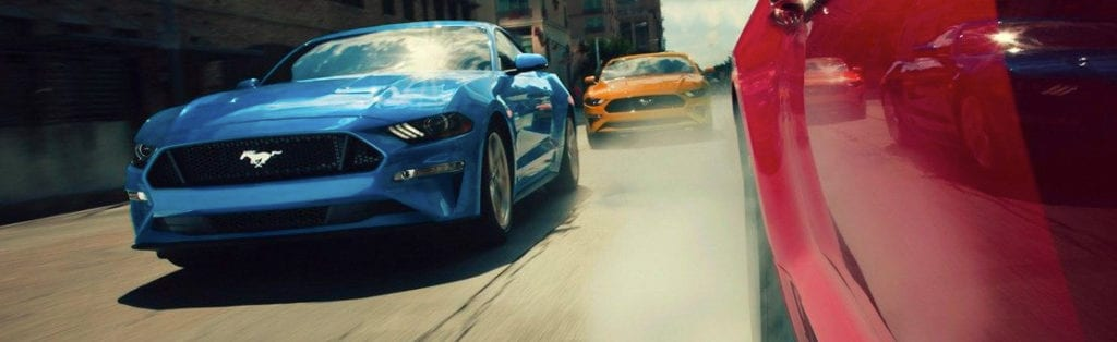 Three Mustangs traveling down a city street