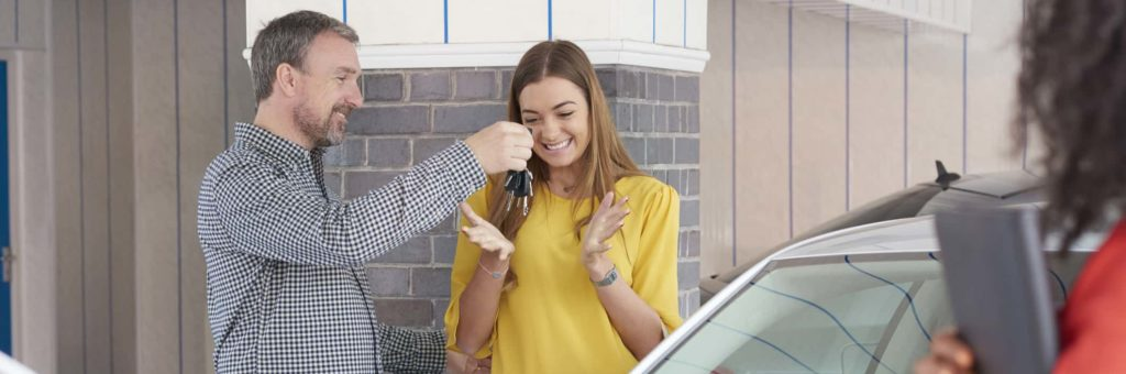 A dad in a plaid shirt gives his daughter the keys to the new car they've just purchased, while the sales woman looks on from the foreground