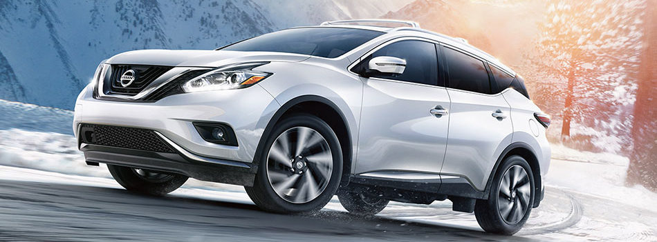 pearl white nissan murano driving on a snowy mountain road