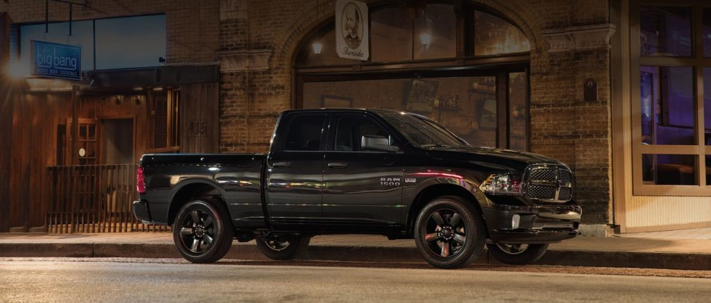 A black 2019 RAM 1500 parked outside a closed shop at night