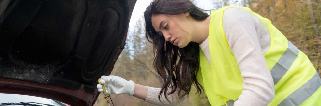 A young woman in a white shirt and yellow vest bends over her open engine and checks her oil