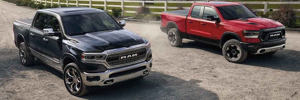 Two Ram 1500s parked outside of a farm