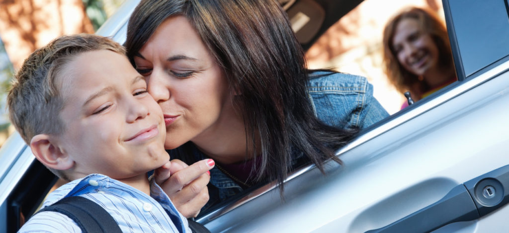 Young boy upset with mom's goodbye kiss at school.