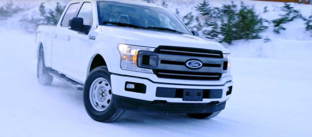 White Ford F-150 driving in the snow