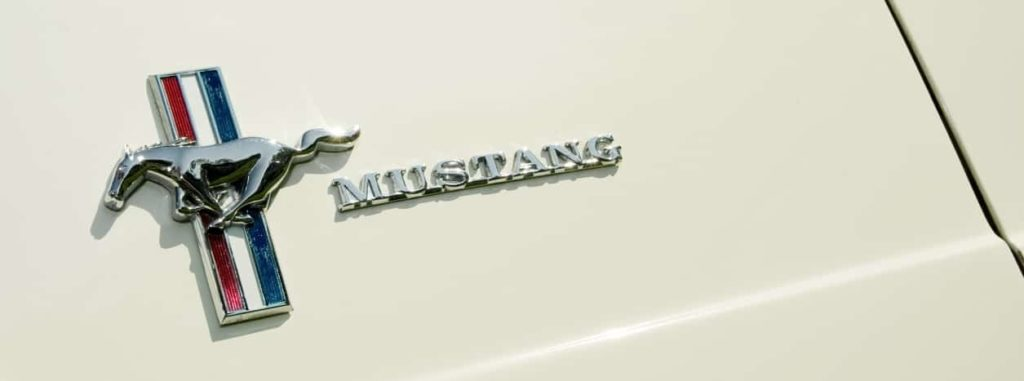 Iconic Ford Mustang badge on a vehicle panel at the Wheels Day auto show, Farnborough, UK