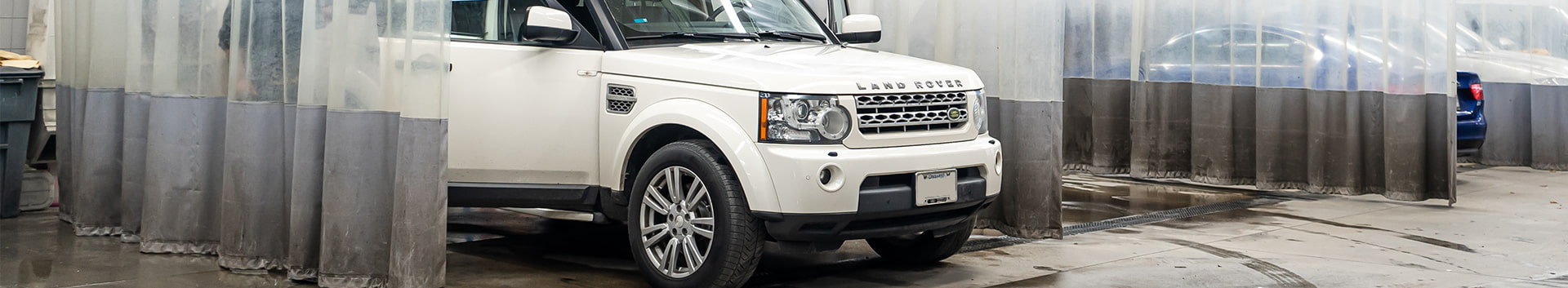 Front 3/4 exterior view of a Land Rover vehicle in the car wash