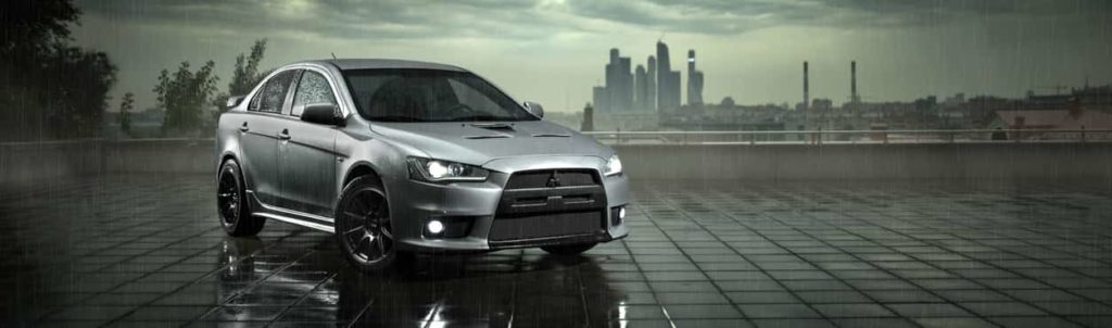 A silver Mitsubishi Lancer Evolution parked in a grey, foggy atmosphere with a slightly tinted sunlit background