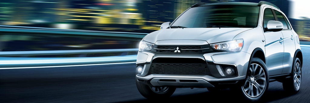 2019 Mitsubishi crossover driving in a blur of a city