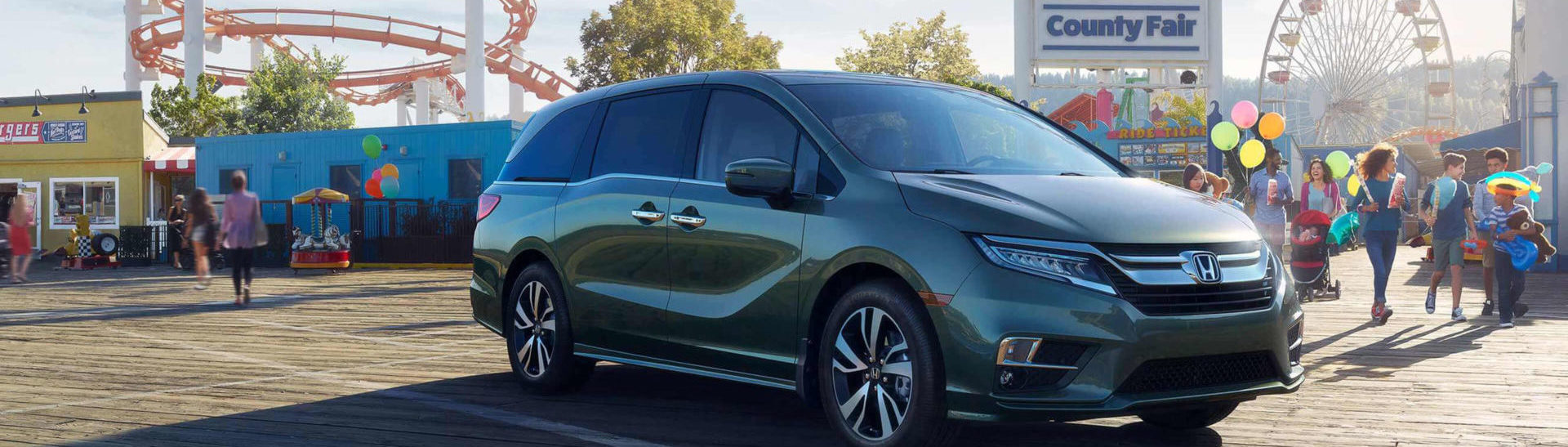 Green Honda Odyssey at the entrance of a country fair