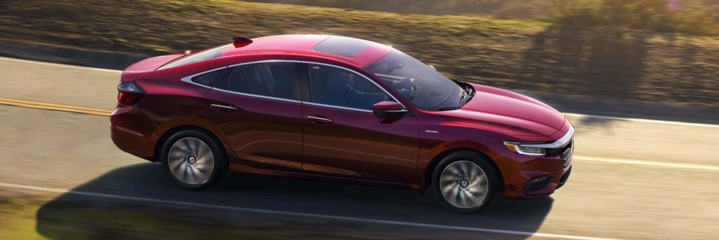 Honda Insight Hybrid driving on a paved road in the country