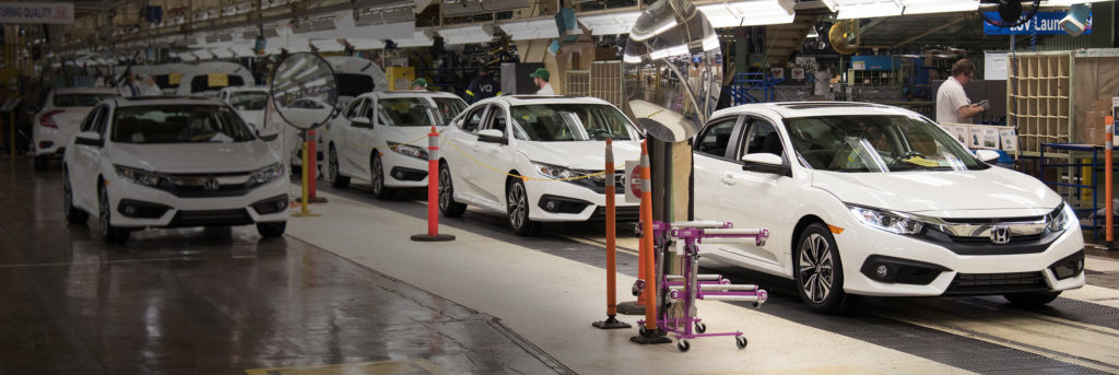 Inside a Honda manufacturing plant with built white Hondas
