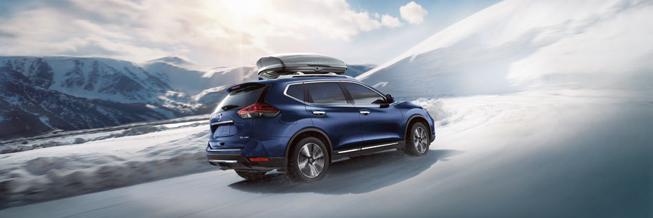 2020 Blue Nissan Rogue with gear on the roof driving on a snowy landscape