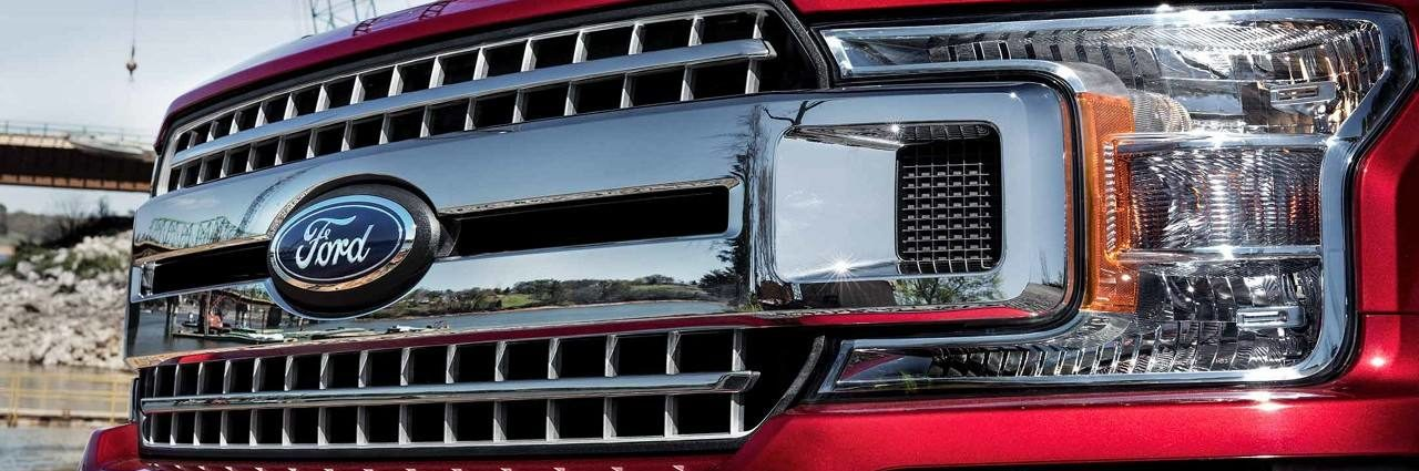 An extreme closeup of the front grille of a red Ford Truck, with the Ford logo prominently displayed
