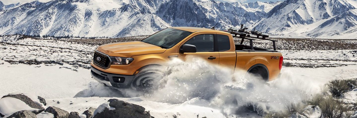 A yellow Ford Ranger, outfitted with roof rack, drives across the snow on a mountain top