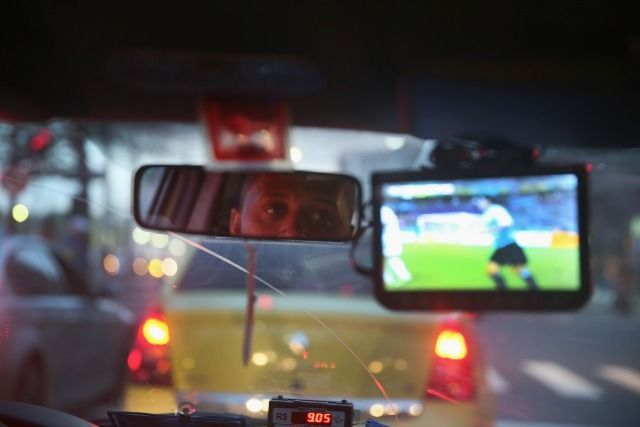 A chauffeur de taxi garde un oeil sur le match Uruguay - Costa Rica. 14 juin 2014, Rio de Janeino, Brésil. ©Photo by Joe Raedle/Getty Images