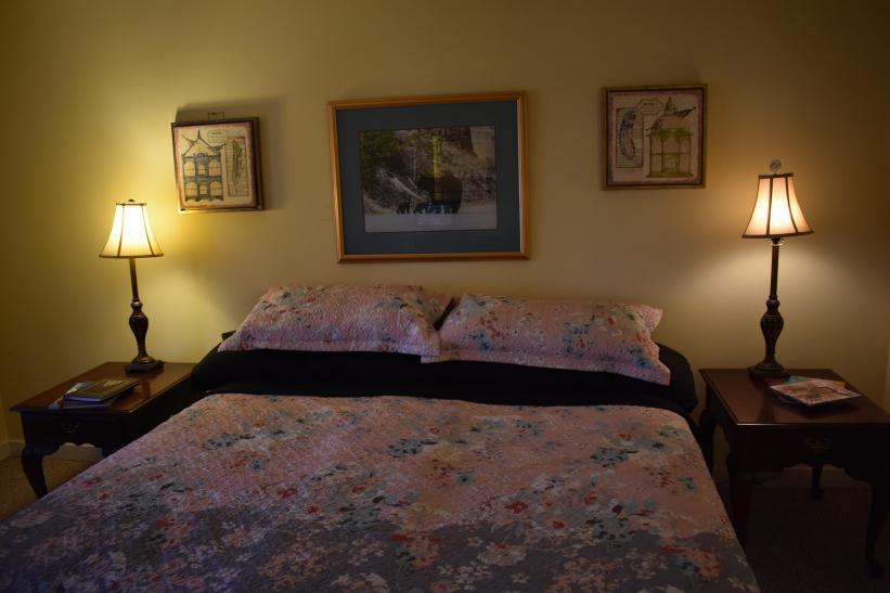King bedroom with full bath, closet, tv, dresser, floor to ceiling window on lower floor