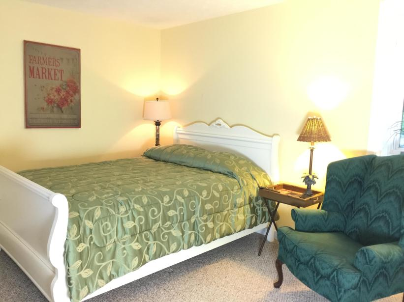 Level 1 bedroom with full bath, side chair, dresser and mirror, tv