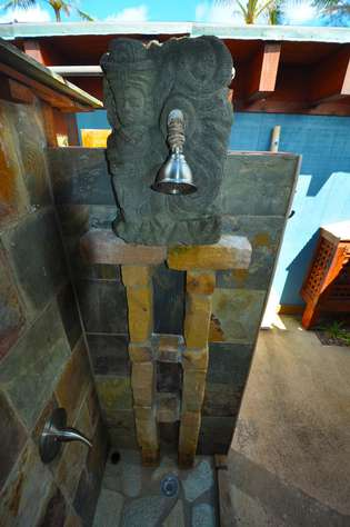 View of Indonesian stone carving of a woman with a water vessel used for the outdoor shower