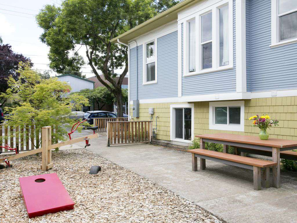 Side yard complete with kids play structures, picnic table, and corn hole!