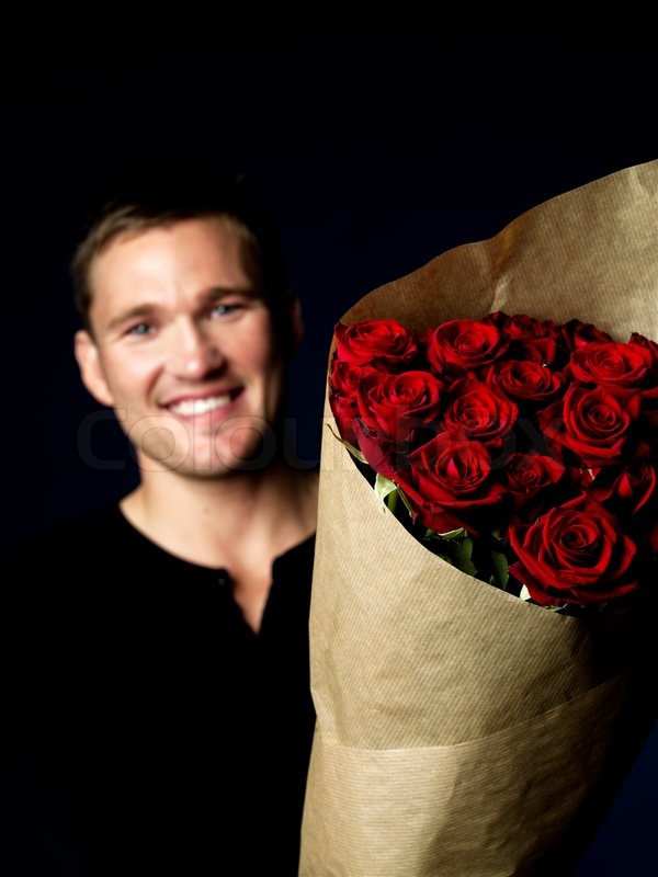 A Smiling Man Holding A Big Bouquet Of Red Roses Stock
