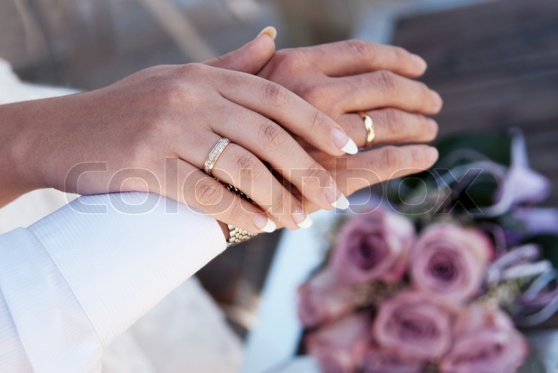 Male And Female Hands With Wedding Rings In The Background