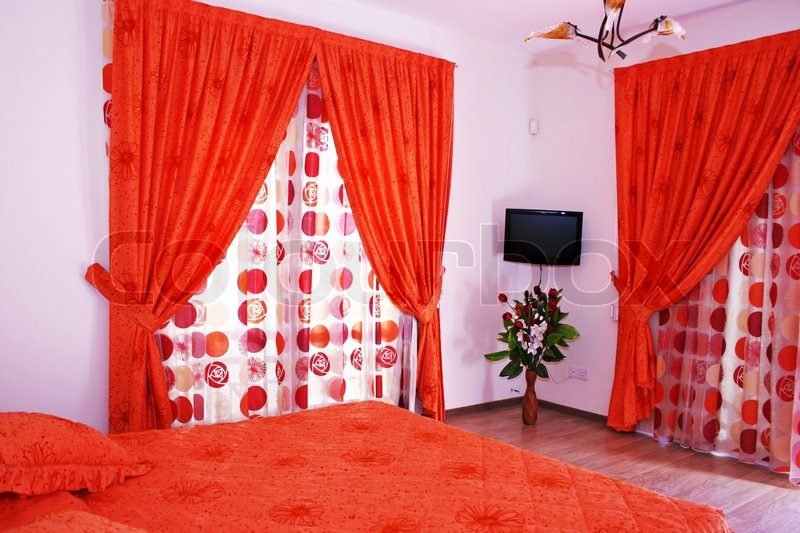bedroom with red curtains, bedspread and flowers | stock photo