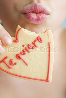 Woman Eating Heart Shaped Cookie Puckering Lips Stock