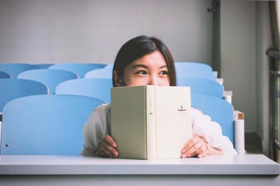 女子学生の学校帳教室の椅子は、幸せな教育リーディング人々を笑顔笑顔