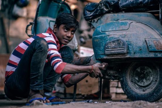 人々の子供の十代の人の修理のオートバイ古い汚いインド人