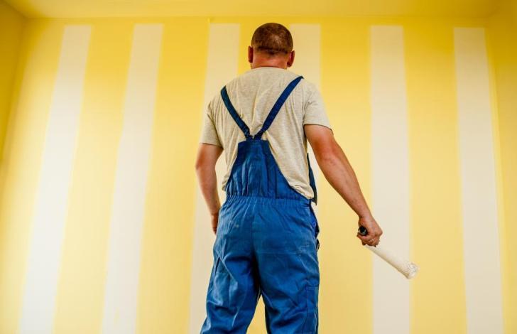 男の男のペイントブラシローラー壁全体の作業工事の改修修理室家の家の人々