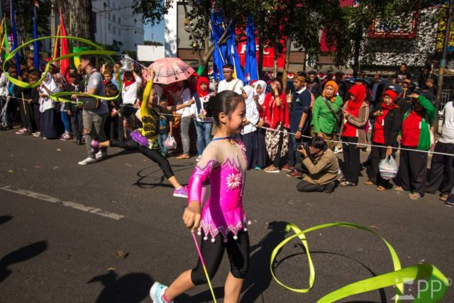 Two young female ribbon gymnysts in parade